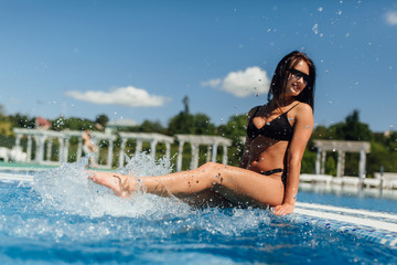 A young happy girl in a black swimsuit creates water springs in the pool. Unfocus picture.