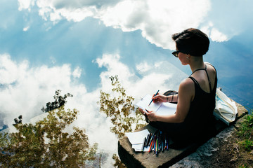 Woman sitting on rock and drawing outdoors
