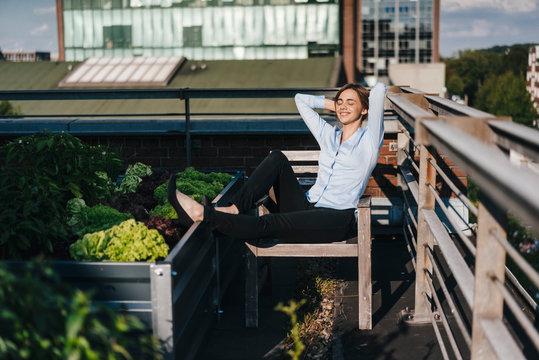 Businesswoman relaxing in his urban rooftop garden