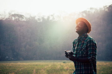 African man traveller holding film camera on a green meadow
