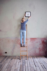 back view of woman on ladder hanging up picture frame in an unrenovated room of a loft