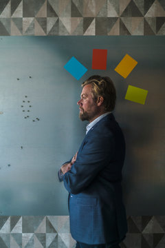 Businessman standing in front of magnet wall with halo of colorful sticky notes