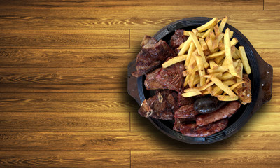 A beautiful plate of grilled steak and sausages with french fries on a wooden table