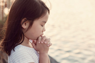 Multicultural little girl praying with sunflare background Wall mural