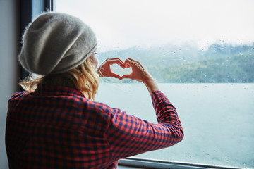 Chile, Hornopiren, woman shaping a heart with her hands at the window of a ferry