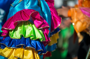 Abstract view of samba dancers in colorful frilled costumes at a daytime Carnival street party in Rio de Janeiro, Brazil