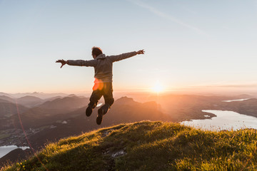 Austria, Salzkammergut, Hiker on mountains summit jumping for joy