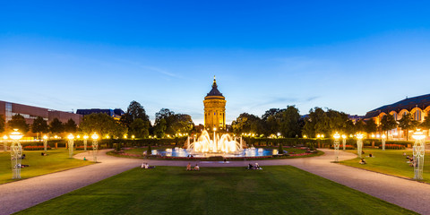 Germany, Mannheim, Friedrichsplatz with fountain and water tower in the background at blue hour
