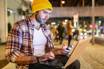 UK, London, man using phone and laptop out in the city at night