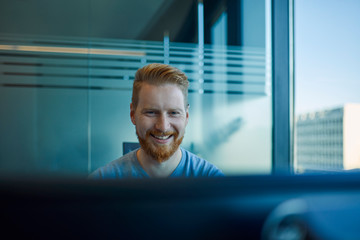 Happy businessman at desk in office