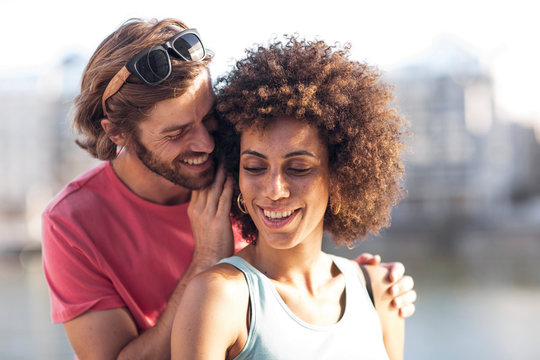 Happy young couple, man whispering into woman's ear