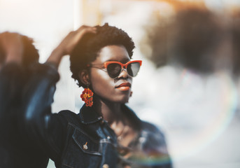 True tilt-shift portrait of a young beautiful African female lit by the sun outdoors; charming fancy black female in sunglasses and with earrings leaning against a glass surface, selective focus