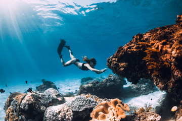 Woman freediver with fins and corals. Freediving underwater in blue ocean