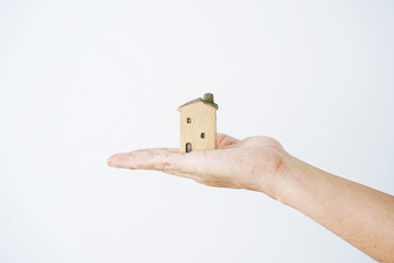 Small house in human hands on a white background.