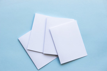 Blank portrait mock-up paper. brochure magazine isolated on blue, changeable background / white paper isolated on light blue paper.