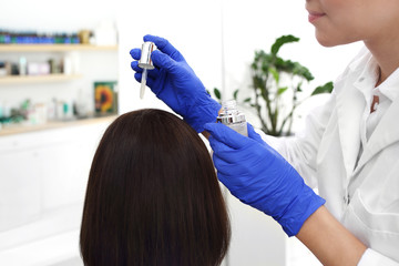 Zabieg przeciwłupieżowy. Pielęgnacja włosów. Dermatolog nakłada preparat leczniczy na skórę...