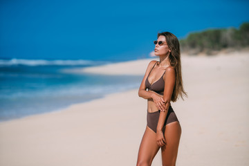 Sexy tanned model with sunglasses in brown swimsuit posing on white sandy beach