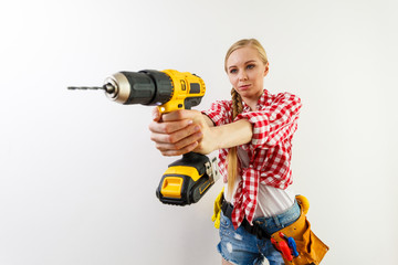 Woman using drill on wall
