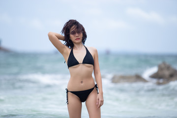 Young beautiful asian women In black bikini posing standing in the sea.