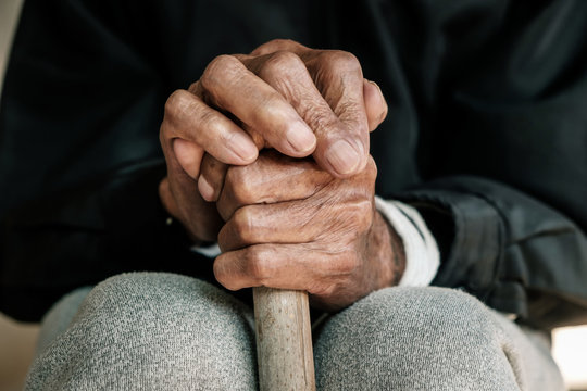Asian old man sitting with his hands on a walking stick