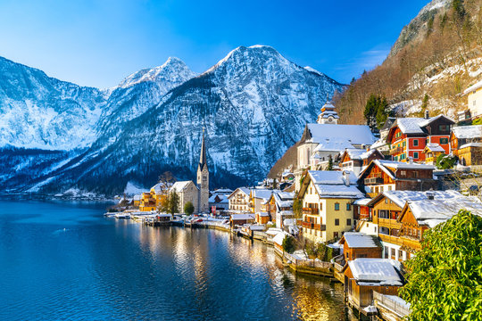 Classic postcard view of famous Hallstatt lakeside town in the Alps with traditional passenger ship on a beautiful cold sunny day with blue sky and clouds in winter, Salzkammergut region, Austria