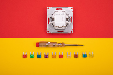 Set of electrical tool and white socket on colorful background