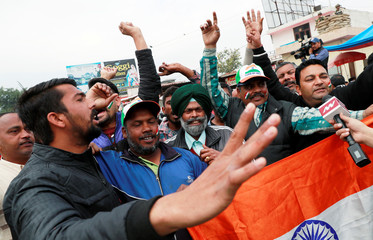 People shout patriotic slogans before the arrival of Indian Air Force pilot, who was captured by Pakistan on Wednesday, near Wagah border, on the outskirts of the northern city of Amritsar