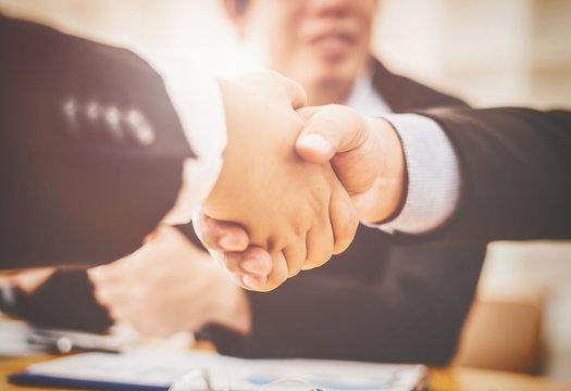 Asian businessmen friends join hands shaking