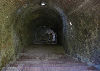 Tuinposter Tunnel Elderly couple walking through a dark tunnel