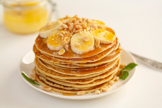 Sweet Homemade Stack of Pancakes with banana, nuts and honey. Delicious breakfast.