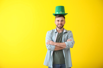 Handsome young man with green hat on color background. St. Patrick's Day celebration Wall mural