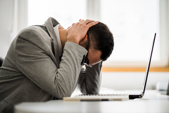 Young businessman is tired of overwork. He is depressed.