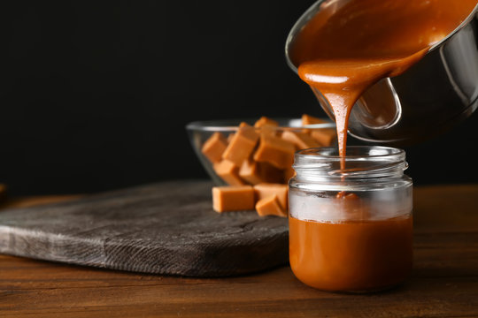 Liquid caramel pouring from pot into jar on table