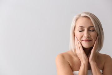 Mature woman giving herself face massage on light background Fototapete