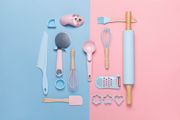 top view of a set of kitchen utensils for baking on pastel pink and blue background