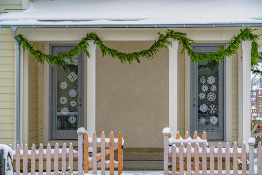 Snowy home with Christmas decals and garland