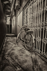 Old bicycle in black and white. Bike left at the fence on the street