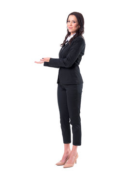 Smiling elegant business woman in suit inviting with welcome hand gesture. Full body isolated on white background.
