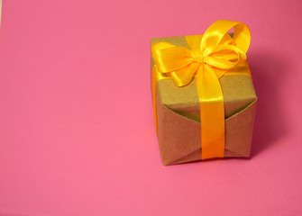 Small present box on a pink background. Kraft paper. Suitable for International Womens Day
