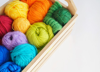 Colorful woolen balls of yarn are in the basket. Needlework. Knitting.