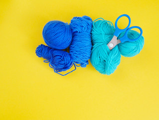 Blue ball of woollen thread. Threads, wool, blue and turquoise colors with a pair of scissors.