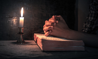 Close up hands of man praying on bible with light of candle. christian concept.