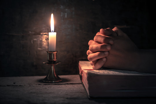 Close up hands of man praying on bible with light of candle on wooden table at worship room. christian concept.