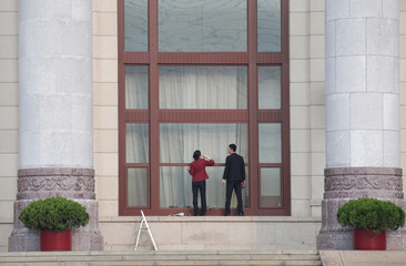 Attendants clean a window of the Great Hall of the People, the venue of the upcoming NPC and CPPCC, in Beijing