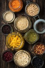 Photo sur Aluminium Cereals, Legumes, and beans in glass jars on dark wooden table.
