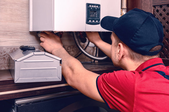 A young skilled worker regulates the gas boiler before use.