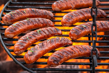 Delicious sausage on grill with herbs and spices Wall mural
