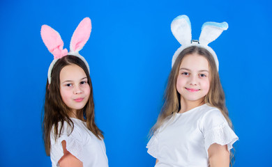 Dressing is a style of life. Fashionable small girls in Easter style. Cute children wearing bunny style headbands for Easter part. Easter fashion style for kids
