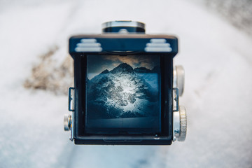 view on the mountain scenery through the viewfinder of the old camera photo. Photographer of the old school takes on a retro film camera