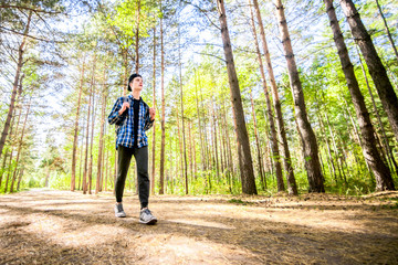 A young man is taking his journey through a green forest.